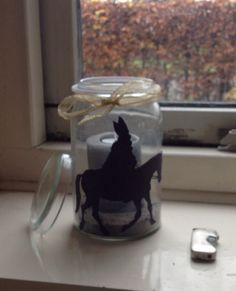 Silhouet van Sint met paard op grote weckpot geplakt. Scherpzand in de pot en kaars met waxinelichtje erin. Mooie strik erom en klaar.