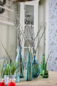 Bright fresh coloured glass bottles with simple flowers make a stunning table piece x