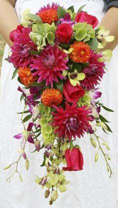 Cascading Bridal bouquet in orange pink and green. Dahlias, roses, dendrobium orchids and bells of ireland.