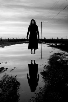 This photo is quite ominous. With just black and white, along with the girl floating above the water and having her reflection be completely black, it gives off a creepy vibe.