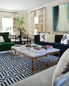 Chic living room design featuring a graphic blue and white flat weave rug, blue velvet sofa, glam green velvet chair, white marble and brass cocktail table, and an abstract painting in blue, beige, and green - Living Room Ideas & Decor