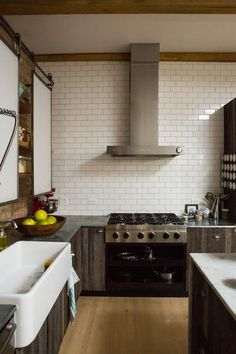 Sliding doors conceal shelving, vintage farm sink, wall of subways - Ellen & Greg's Renovated Loft Kitchen Kitchen Tour Small Kitchen Diner, Loft Kitchen, Kitchen Dining, Kitchen Cabinets, Rustic Kitchen, Beautiful Kitchens, Beautiful Interiors, Sliding Cupboard, Cupboard Doors