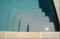 """Things That Inspire shares this info: """"...the steps to the pool show the different colors that the Pebble Sheen French Grey takes on at different depths. It was a medium gray when it was installed, without water – and as seen on the first step, that's how it appears in very shallow water. However, when there is water at greater depths ( which is the majority of the pool ), the color appears a beautiful and sophisticated blue – not a greeny blue, but a turquoise!"""""""