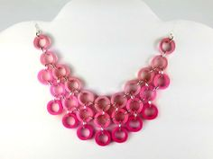 This ecofriendly bib necklace features a large cluster of pink rings made from paper quilling strips. The little circles are connected with silver plated jump rings which allows the necklace to keep it's shape. You will be three times as fun and flirty, as this piece boasts three different shades of pink ranging from light pink to flamingo pink to fuchsia. Each ring has been painted in a sealant which makes this necklace water resistant and UV resistant. It is super lightweight.
