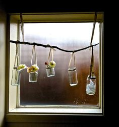 a hanging collection of vintage jars in the window. bright and cheerful