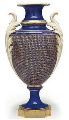 AN ORMOLU-MOUNTED SEVRES PORCELAIN BLEU NOUVEAU VASE ('VASE A GORGES' OR 'VASE A TROIS GORGES') THE PORCELAIN VASE CIRCA 1770-1780, THE LATER SOCLE WITH GREEN MARK FOR 1868 AND DECORATION MARK FOR 1912, THE ORMOLU BASE OF A LATER DATE Gilt overall with a tight diaper pattern, gilt dentil rims
