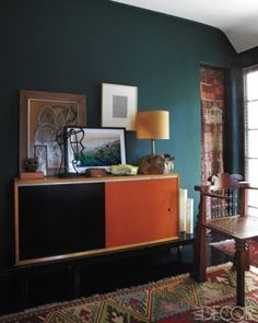 Old rug as doorway curtain and deep green wall with orange console.