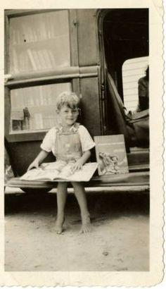 Boy sitting on Beaufort Hyde Martin Regional Library Association bookmobile, July 8, 1942 ^cs