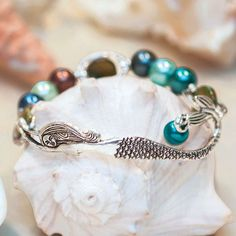 """Mermaid Round Bracelet: This ocean-inspired bracelet features beautiful hand painted sea-colored beads on a stretchy band with a swimming mermaid charm encircling your arm. Made of pewter and hand painted beads. Mermaid charm 3""""L x ½""""W. Stretch one size fits most."""
