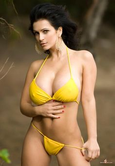Denise Milani wearing her yellow bikini at the beach, but judging by her hard nipples, it might be a little too cold to try the water.      ...
