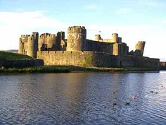 Caerphilly Castle, Wales. At one point the town grew up to the castles walls and it was a total ruin. They have now returned it to much distance it was from any other buildings, and partially restored the building. It is a place to let ones imagination run wild!