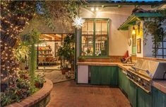 outdoor kitchen feels like extension of the home. tree in middle of courtyard