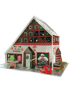 Stitch this detailed shoppe using 10-count plastic canvas and embroidery floss. It has open windows to peek in and a removable roof for easy access. You can decorate the inside as well as the outside. Pattern includes color photos, tips, graphs  Learn how to make this North Pole Shoppe in Plastic Canvas Patterns (aff link)