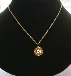 """I was immediately charmed the minute I laid eyes on this necklace -talk about the perfect Valentine's gift! The nest itself is made up of 100% sterling silver and lttle fresh water pearl """"eggs"""" represent each child. Made up of 100% sterling silver, the nest measures just over 1/2 inch in diameter and the chain 17.5 inches. A shorter or longer chain is available to purchase with no extra charge. Necklaces are customizable for mothers with 1-3 children and are available in antiqued brass ..."""