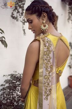 Yellow raw silk gown with a teal floral border at hem, shoulder strap and pockets with a blush soft net dupatta