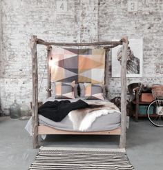 A PATCHY THROW AND CUSHIONS AT KOSKELA | RAW WOOD 4 POSTER | EXPOSED BRICK
