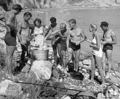 """Lifeguard Lorrin """"Whitey"""" Harrison places an octopus in a pot for a beach cookout via LIFE Magazine. Though captioned as Santa Monica, the shore more closely resembles Leo Carrillo or County Line because of the rocky beach and kelp beds. California History, Southern California, Lifeguard, Venice Beach, Vintage Santas, Life Magazine, Gold Coast, Santa Monica, Historical Photos"""