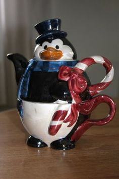 Christmas Penguin tea for one stacking teaset (teapot and cup) in shape of penguin wearing a top hat and scarf and carrying a candy cane that forms the handle, ceramic