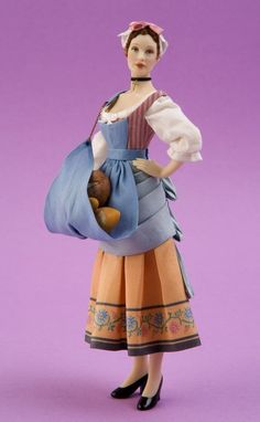 NAME: Giustina  PERIOD: Late 19th century  PRICE: 500 euros  Baker woman, replica of an Italian old print. The skirt and bodice are made of silk, exclusively printed for Carabosse Dolls by Les Chinoiseries. Bread by the Spanish artisan Montse Moreno.