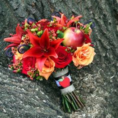 Round, fresh floral bridal bouquet in red, orange, tangerine, burnt orange, brown, and green. This rose, lily, hypericum berry, waxflower, fern shoot, and apple bouquet was wrapped in a burlap stem wrap and created for an apple themed, cider mill wedding. Designed by Kim at Floral/Something Spectacular, Warren, MI. Photo: Urban Fire Studio.