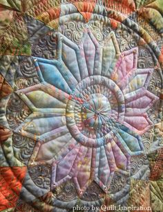 Close up of the center of This Midnight Dahlia (a pieced Dahlia on a black background) won Elaine Putnam First Place, Pieced – Medium. The quilting, by Gina Perkes, was awarded a special ribbon for Exemplary Machine Quilting (Track Mounted).