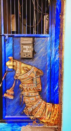 Artistic blue door with a painted camel in Delhi, India.