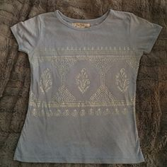 Free People Shirt Beautiful Free People short sleeved shirt in baby blue with silver sparkle design. Pictures don't capture how lovely this top is. Excellent condition. Labeled as small but fits like XS Free People Tops