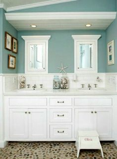 Aqua and white bathroom with seaside cottage feel and river rock floor, really cool!