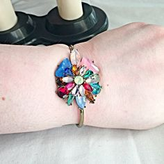 """NEW CRYSTAL FLOWER MULTI COLOR GOLD BANGLE BRACE Delicately designed titanium multi colored Crystal open cuff bangle copper bracelet. 1 1/4"""" opening. Measurements: 2.5 X 1.5"""" NO TRADES ❌QUESTIONS FROM NON SERIOUS BUYERS DO NOT ASK ME TO CREATE A BUNDLE UNLESS YOU INTEND TO BUY ✂️DO NOT LOWBALL ⛔️NO PRICE COMMENTS ⁉️PRICE IS FIRM AND REFLECTED ON FEES AND OUT OF POCKET FEES Boutique Jewelry Bracelets"""