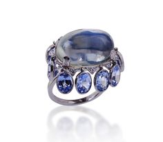 A 20.60 CARAT CABOSCHON SHAPED MOONSTONE WITH 10.09 CARATS IN OVAL SAPPHIRES AND .22 CARATS IN DIAMONDS SET IN PLATINUM