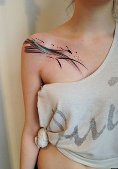 Abstract tattoo under the right clavicle.