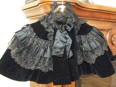 "Victorian Era Cape or Mourning Gown Cape with Lace. OK, doesn't technically look like ""black"" lace, but it does seem to be a greyish tone, over black."