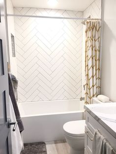 Guest shower. Herringbone white subway tile gray grout. Gold accent: