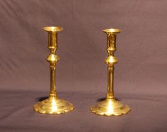 Pair of George II petal based Brass Candlesticks with shaped drip pans above a knopped stem. Circa. 1740