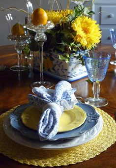 lemons in glass candleholders...yellow rattan mats and lovely white, blue and yellow plates topped by a floral napkin