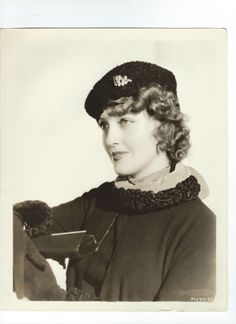 """Back of the photo states: """"HOLLYWOOD FASHIONS ON PARADE...Black Persian lamb, matching the trim on her chic suit, created this smart cossack type hat worn by Jeanette MacDonald, lovely Metro-Goldwyn-Mayer star. An ornament of sterling silver is caught at the left side, and is the hat's only trim. - ESCANO COLLECTION"""