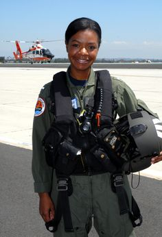"""Lt. j.g. Lashanda Holmes stands in front of an MH-65 Dolphin helicopter at Air Station Los Angeles. Holmes, from Fayetteville, N.C., is the first female African-American helicopter pilot in the Coast Guard. 'SEMPER PARATUS"""""""