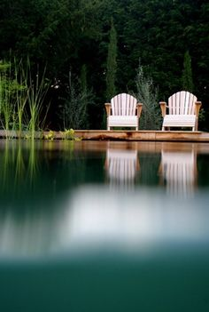 Natural swimming pool, white beach chairs, water, reflection