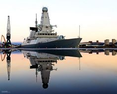 Royal Navy Type 45 destroyer HMS Defender is mirrored in water following a downpour on the dockside in Glasgow,