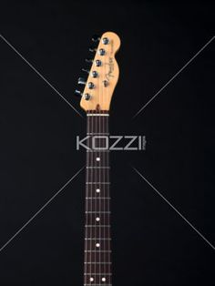 fret board and peghead of a guitar. - Close-up shot of fret board and headstock of a guitar against dark background.