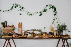 Simple greenery on the wall above dessert table