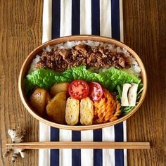 ご飯を横半分に詰めたお弁当。鯖の味噌煮缶そぼろをご飯に乗せ、レタスで仕切り、おかずを縦にきれいに並べています。並べ方をいつもと変えるだけで、同じ曲げわっぱでもまったく違う雰囲気に♫