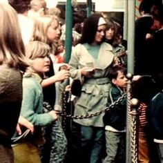 Priscilla Presley in white headband with sister Michelle's face right next to her on right at Disneyland mid 60's..