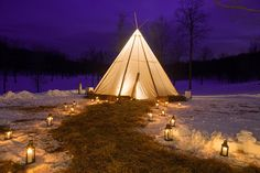 Jasper Madison's TipiMarqui lit up at night in winter.  Perfect for any time of year the TipiMarqui is the perfect tipi for your next gathering.