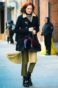 A black is worn over a striped turtleneck with a top handle bag, olive green pants, and black boots