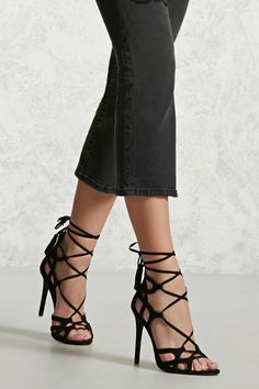 A pair of faux suede shoes featuring cutout sides, a lace-up front, an ankle-wrap with tassel ends, an open toe, stiletto heels, and a zippered back.
