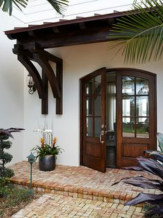 Florida beach house exterior - we just can't get over those wooden front doors!  The whole house is incredible. #InteriorDesign #exterior