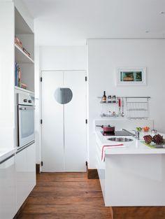 """Cozinha 3. A porta bangue-bangue facilita a entrada para a cozinha principal. """"Prática, a escotilha deixa entrever a passagem das pessoas, evitando acidentes"""", diz Renée. Usados como arremates dos móveis, os rodapés de madeira medem 15 cm de altura."""