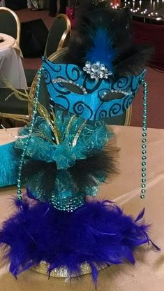 Directly incorporating the theme as a centerpiece is always a safe go-to option. The one pictured here is elaborate and beautifully adorned, yet achieves appropriate the height so it doesn't block across table communication. New Year's Eve Masquerade Party, Masquerade Decorations, Masquerade Theme, Masquerade Ball, Sweet 16 Decorations, Ball Decorations, Balloon Decorations Party, Moms 50th Birthday, Birthday Bash