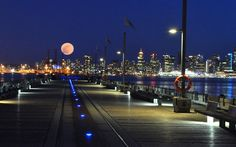 Night view of Vancouver from the North Shore, with a full moon rising over the city skyline. UK Telegraph  Mike Klajnert
